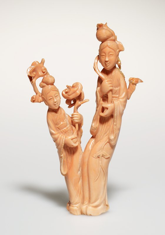 Pair of carved coral figures holding branches of flowers; green silk standard. Pink coral.