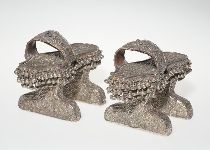 Pair of sandals; made of wood with high pieces under heel and two to rise feet about 5 inches above floor. Covered with silver? which has been pressed into a mould to give repousse effect. The designs are conventionalized floal and geomtric and cover the entire surface, also the leather strap over the instep. Around the sole are two rows of tiny silver bells; around heel and two three rows; on top of band over instep is a small boss of silver.