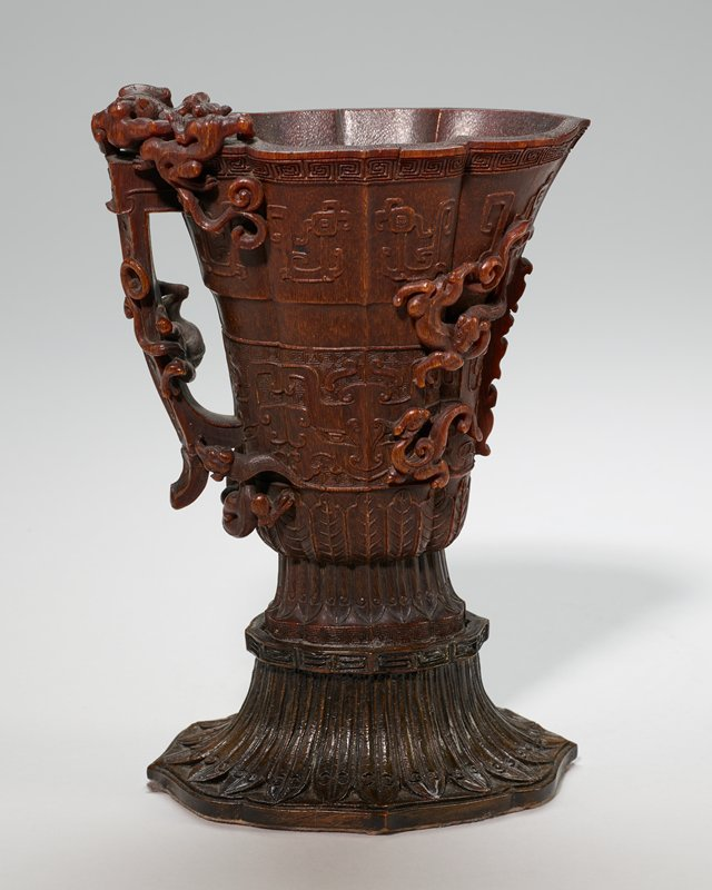 carved rhinoceros horn libation cup; in form of an old bamboo incense burner; it has side coiled dragon handle, and is decorated with designs of conventional animalistic heads and cloud patterns enclosed in borders of geometrical key patterns; carved wood base