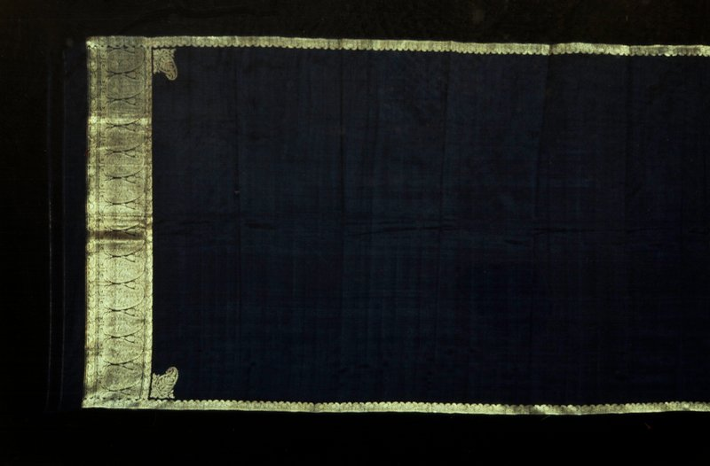 sari, black silk. Widfe woven border of palmettes at one end and narrow border on both sides