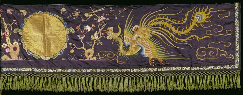 Temple banner of black satin embroidered in gold and silk threads with two phoenixes facing a gold disk. Finished with a narrow floral border, and at the bottom with green silk fringe. Lined with blue cotton.