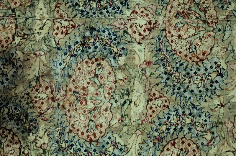Piece of loosely woven linen material embroidered in all-over pattern of dull red flowers with spiked blue leaves fitting around each flower. Embroiderd with silk in surface darning stitch. A border of leaves and flowers finishes the bottom. Fragment of a larger piece. Linen.