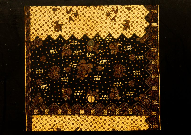 Sarong, or skirt, of batiked cotton material with front panel of dark blue and dark blue borders at top and bottom. Ground of light and dark tan squares and circles in all-over pattern. Cotton.
