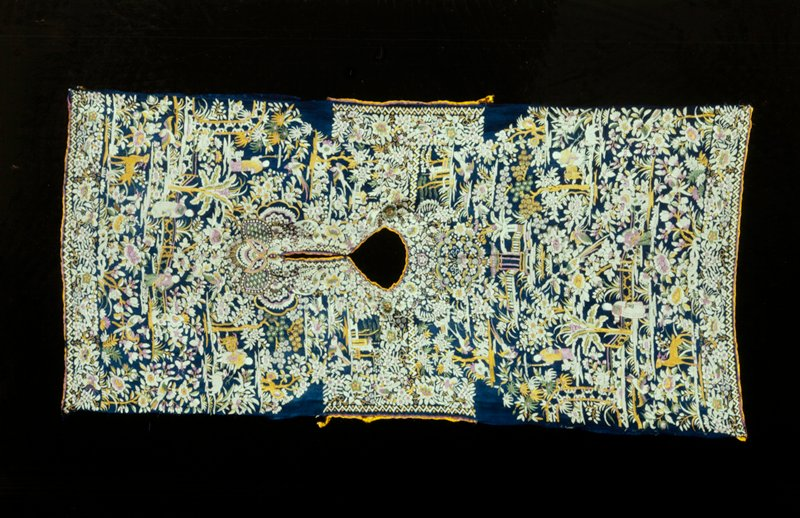 Child's Shirt of dark blue silk embroidered with satin stitch in Chinese landscape pattern of flowers, birds, men and animals. The seams at both sides have been ripped open. Neck, arm holes and hem are finished with bands of lavendar and yellow silk.