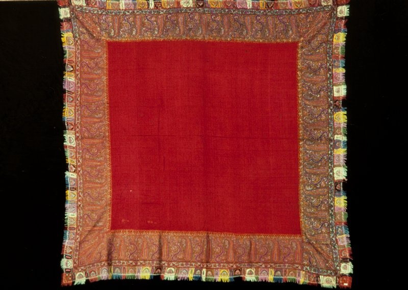 Shawl with plain red woolen center and separately woven border with palmette and tree patterns, in shades of green, red and purple. Finished with a narrow fringed border of patchwork squares and embroidery. The border is added so that on two sides the back, or wrong side of the material shows.