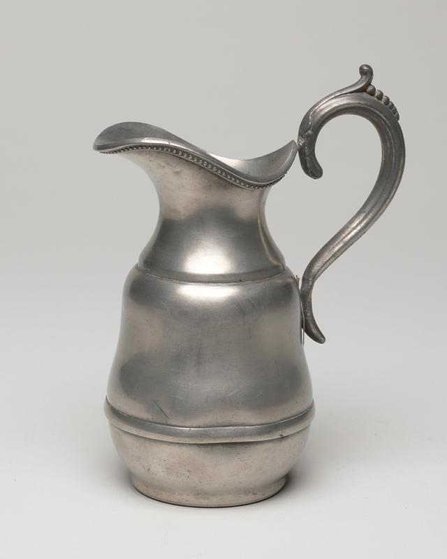 jug decorated around rim and on handle with beading; this shows influence of silversmith design