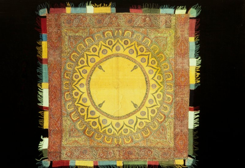 sqaure shawl, small, with ground of yellow wool, the central portion of which is decorated by large circles, butha and lotus; border of fine floral design woven separately and added; supplementary border of fringed strips of colored wool