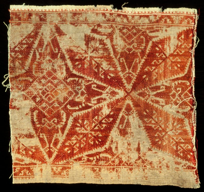border, piece of tan linen embroidered with henna red silk in a star and lozenge design contained in a larger diamon-shaped motif; narrow border of running triangle motif; fragment of a larger piece