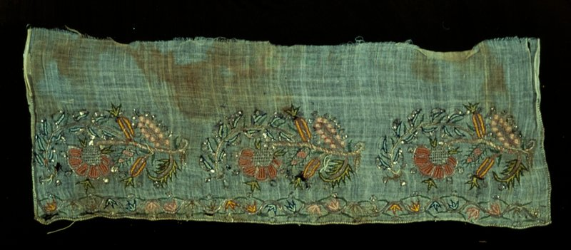 towel end of loosely woven cotton embroidered with three sprays and having at each end a running leaf design as a border; rose, blue, green and metal threads the bottom and sides whipped with gold thread; silk on cotton