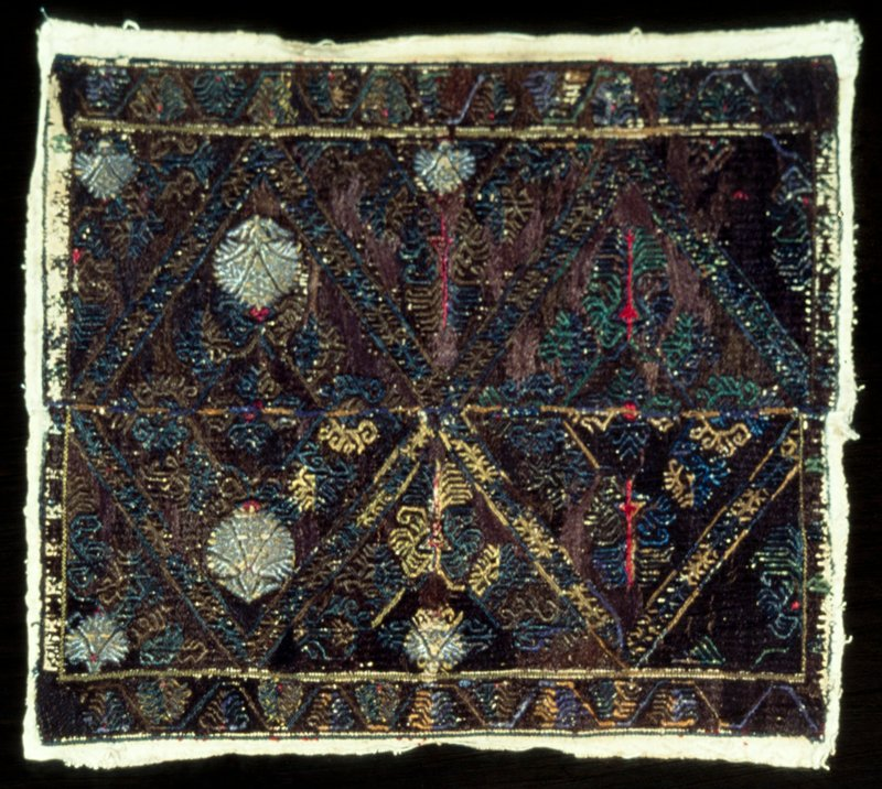 Square of canvas entirely embroidered in dark blue, green and brown floss and gold metal threads in flower design. Piece composed of two strips joined together.