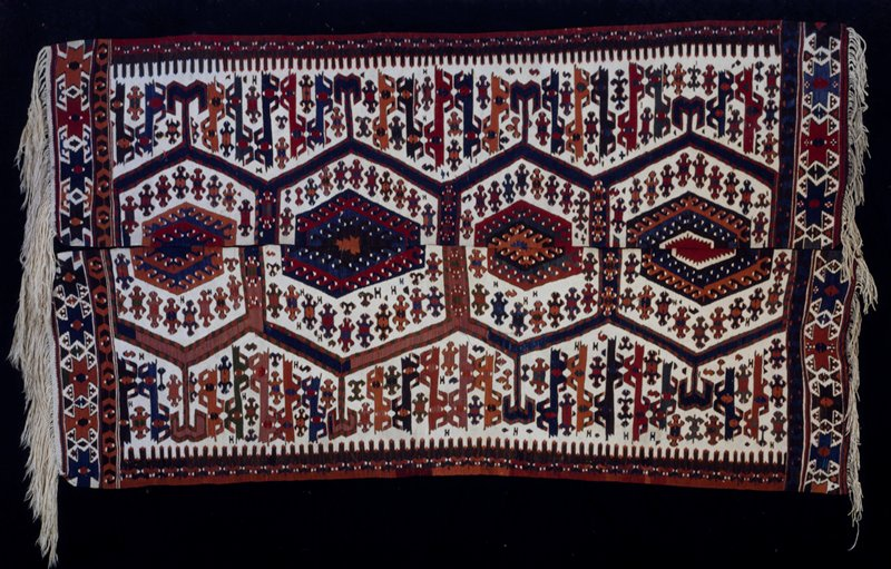 Khilim rug woven by Karamanians- nomads of Turkoman descent. Dark blue ground with bold octagon designs in red, brown and green. This Khilim has been woven in two pieces so irregularly that when placed together the octagons, woven half upon each piece, do not coincide. There is a long fringe at one end and a short one at the other.