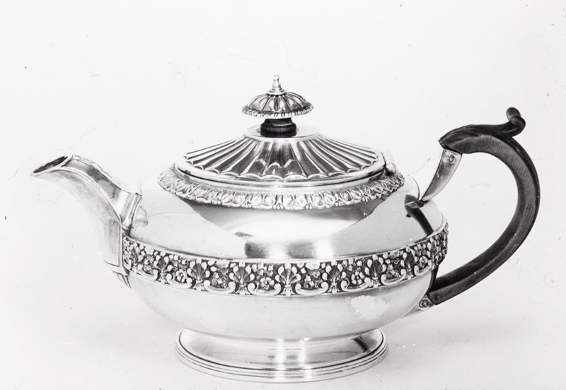 teapot, round, decorated at top and around the middle with a band of strap mount work in leaf and grape design; the spout is joined to the body by a shell shape, and the cover and finial are decorated with radiated fluting; the finial is also gadrooned around the edge; wooden handle attached to body by wedge-shaped piece of silver
