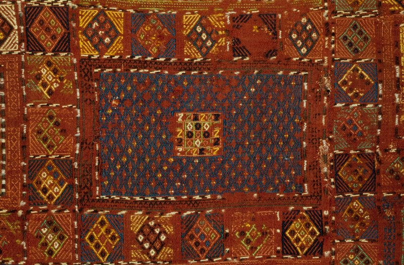 Embroidered sile Khilim of the type used for hanging, or coverlet. Faded henna field embroidred in squares which contain various geometrical designs. Made in two pieces and sewed together. Border of triangles and squares containing triangles. Short web with knotted warp threads at one end, loose warp threads at other end. Wool.