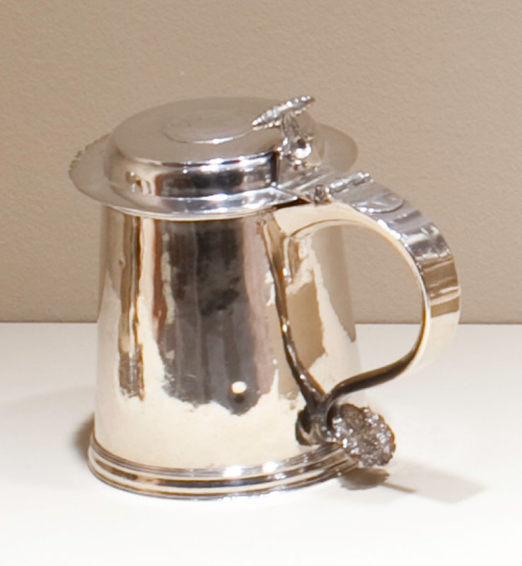 tankard with cylindrical body, flat cover with serrated front edge; coin inset on cover (silver crown of Hungary; S-scrolled handle engraved with contemporary initials [PHJM]); corkscrew thumb piece; handle tip embossed with ram's head