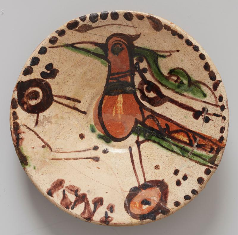 Bowl, shallow; of red earhtenware, glazed and decorated on upper side only; cream-colored ground. Center decoration large burnt umber bird, crudely outlined in brown; green beak ad tail feathers. Border consists of brown dots of uneven size, crudely applied. Low foot. From Amol. Strong resemblance to bowl in Sam Lewisohn Collection, N.Y.C., shown in Illustrated London News, Jan. 10,1931, P.63. Low foot, unglazed.