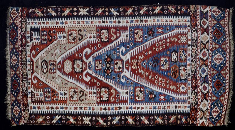 Rug, small, Khilim; green ground with a pyramid design repeated four times in red, blue, red and grey. The side borders are white with an indented design at the edges. There are four narrow borders at the bottom. The open spaces in this rug are not very noticeable.