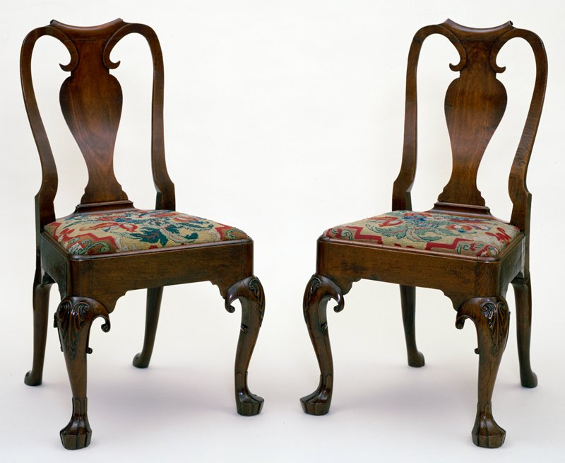 chairs, pair of, with fiddle backs; cabriole legs, the knees carved with a simple leaf design. Dutch grooved feet; slip seats upholstered in old wool needlework in shades of red and bright yellow cross stitch.