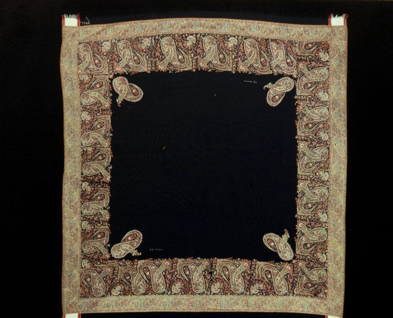 shawl, four borders and corner butha woven seperastelt and stitched to black center. Pieces of embroidery carry the design over into the center; design of interlacing buthas in several colors, chiefly red; border design is a simple repeat not fitted around the corners; fringe at ends
