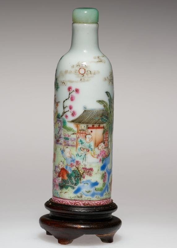 Snuff bottle, cylindrical, painted white porcelain with stopper and stopper and stand. Scene of a house and figures picnicing beside a pool-green, red, yellow, blue, and a narrow band of scroll decoration at the bottom; jade stopper.