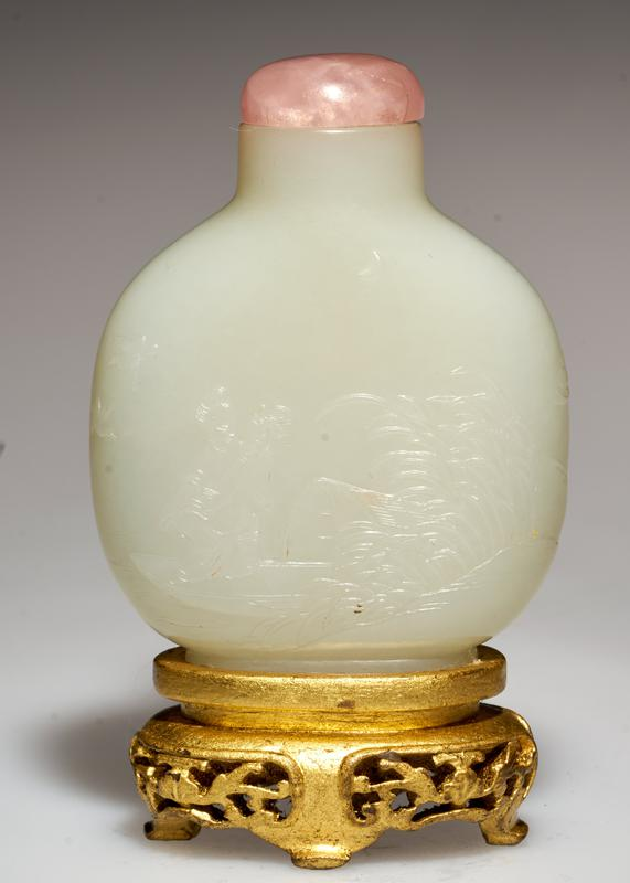 Snuff bottle, white jade carved with a scene which depicts an extended pavillion in the moonlight; spreading branches of trees droop over the pavillion. Pink tourmaline top; gold stand.