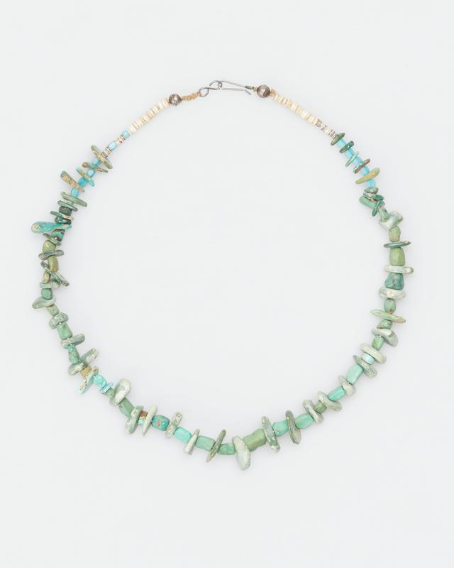 necklace of turquoise beads (wampum) cut in various shapes and finished each end with a series of shell disk and one round silver bead; wire clasp; turquoise