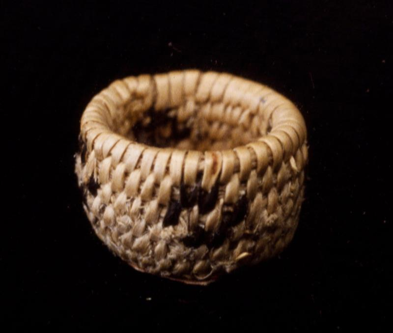 Miniature round basket; coiled. Design consists of a band of four coyote tracks. Colors are natural and black.