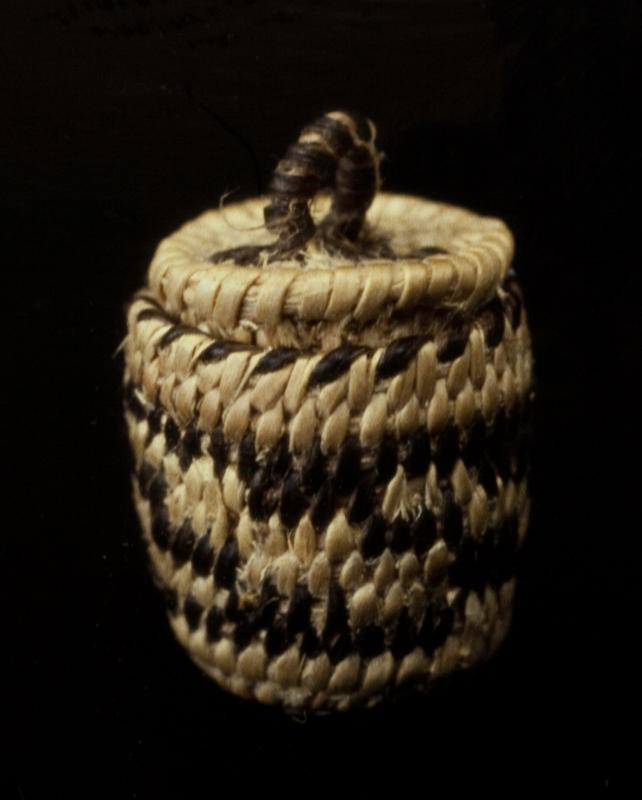 Miniature round basket with cover; coiled. Design consists of a band of stepped horizontal stripes around the sides. Colors are natural and black.