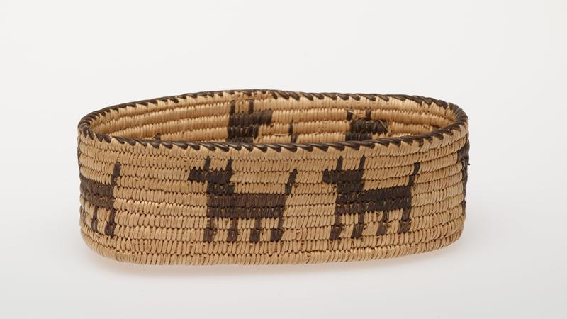 Miniature oval basket with straight sides; coiled. Design consists of a band of animals (probably dogs), around sides. Colors are natural and black.