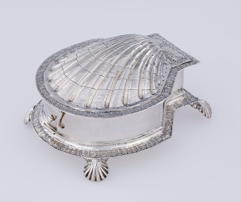 shell-shaped covered spice box; James I; oval body with flat back divided into two sections; ovolo mount, on four shell feet; hinged shell-shaped domed cover with matching mount; clasp and button at front