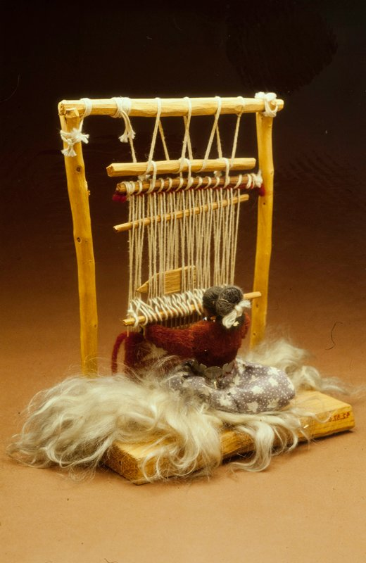 small wooden model of Navajo Indian woman, seated before a loom weaving