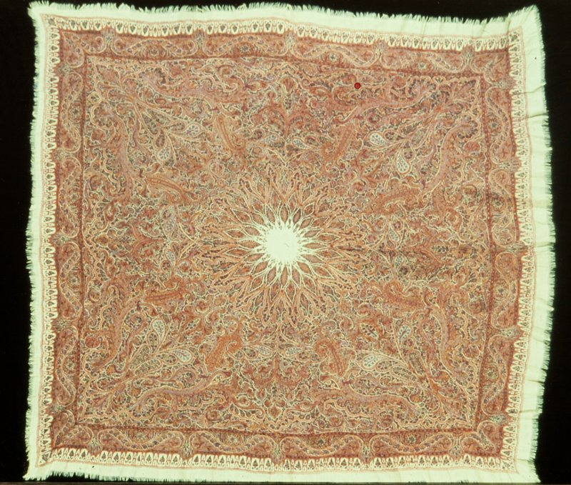 Kashmir, Amli-rumel, or square embroidered shawl, worked in darn and stem stitch in a design of cones and floral arabesque in shades of red, blue, green, and yellow on a white ground. Border of serpentine scrolls and rosettes with outer border of floral panels. Fringed edges. A very fine example. #4 of exhibition.