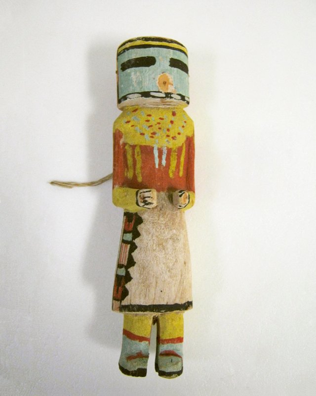 Hopi ceremonial doll, painted; turquoise drum-shaped mask with red spout nose, red and yellow blouse, white skirt decorated at side with band of red, black and blue; yellow socks, turquoise and red boots; twentieth century