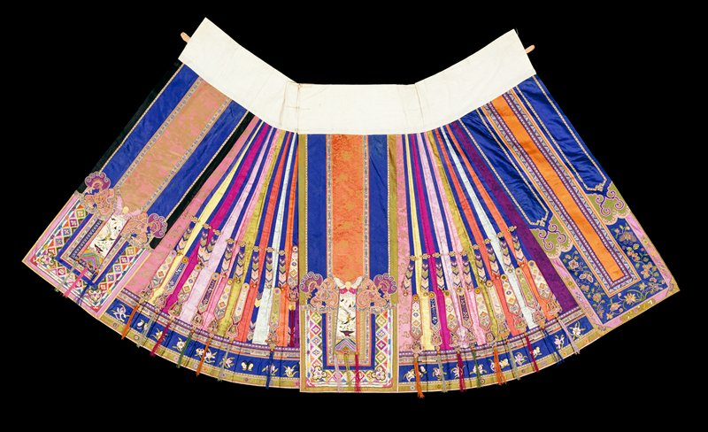 Tibetan Wedding (?) skirt made of strips of yellow, fuschia, lavendar, pink, green , orange, purple, iron red and rose brocaded satin, some with the designs in color. Hanging from the skirt, knife-pleated in side sections, are wavy embroidered strips, finished with bells, tassels, and pearls. Main panels have an elaborate design of applied embroidered borders, braids, applique silk flowers and rosettes on the main and bottom borders. Lining of thinblue silk; an extremely elaborate skirt of quality not often found. Embroidery done in many stitches satin needlepoint, loop, knoot, stem, etc.