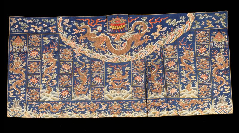 Buddhist priest robe of K'ang Hsi blue k'ossu with gored end. Mnay five-clawed dragons in gold, those in the border having th symbolic universe design below. The small squares representing Buddha's mendicant days are alternately filled with gold dragons and large peony blossoms in shades of red, pink, and green. The shaped gores are filled with peony blossom and trailing tendrils. Upper border contains loose cloud forms and bats in end sections. Colors include green, red, pink, yellow, olive green , puce, mauve, yellow coral, peach and burnt orange. Compare treatment of clouds, wave border and dragons with the K'ang Hsi robes. K'ossu broken in many spots. The squared and gored areas set off with bindings of yellow satin. Lined with thin rose silk. Canopy flap with standard design, at center of upper top.