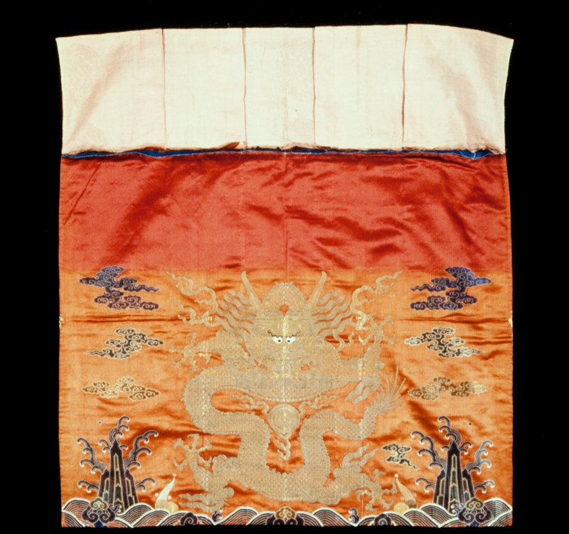 Altar Frontal of brocaded brick red satin. In the main panel one large five-clawed dragon in gold surrounded by loose clouds in shades of green, blue, and tan. Below, a shallow area of rolling waves among which appear the Eight Precious Things. At the top a short pleated valance bearing five-clawed dragons and longevity characters in the panels formed by the pleats. Linings of blue cotton and thin pink silk. Illegible seal on back.