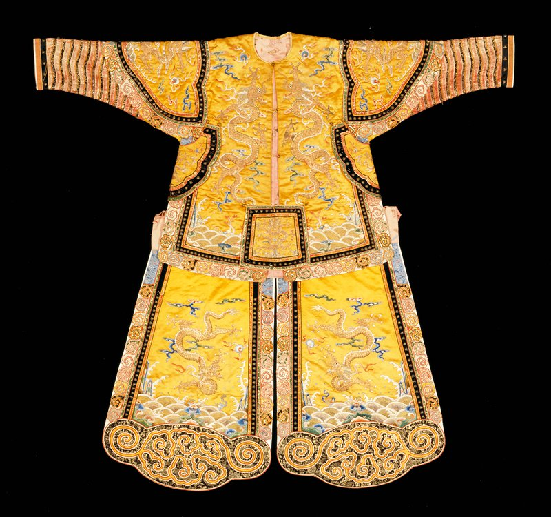 Actor's short coat of embroidered gold-colored satin. Five four-clawed dragons in couched gold thread. In the field are thin, loosely-drawn clouds in shades of blue, green, pink, red, mauve, and peach color, cone in satin stitch and outlined with couched gold threads; scattered among the waves are loose clouds, coral branches and symbols of the Eight Precious Things. Under the arms are attached shaped, embroidered panels with gold dragons, and at lower front of coat a quare panel of the same. These, and the shoulder area of the sleeve, are bordered with a band of black velvet studded with metallic bosses. Outer border of 'tiger claws' in fragments of colored brocade like that in Buddhist priest robe C.80 (42.8. ) Gold and red brocade sleeves, much worn, banded with black and gold brocade. Lining of painted pink silk. Light padding. See matching skirt, 42.8.127B. Matching skirt Actor's chaps of embroidered gold-colored satin to match coat 42.8.127a. They are made of two shaped side panels attached to a deep waist band of the painted pink silk with which they are lined. One four-clawed dragon in couched gold on each panel. Shaped border with appliqued scrolled pattern of black and gold brocade edged with a narrow band of white braid and bound with red satin. Front and sides banded with tiger claws of brocade, as on coat. A handsome and well-preserved costume. Compare genreal drawing with K'angHsi group. Note The actor wearing these chaps was supposed to represent a man on horseback.