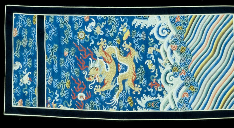 Panel of medium blue k'ossu with five-clawed dragon, bats, clouds, symbols, and eternal sea motif, cut from a court robe. the panel is bordered with a band of black satin bound with ivory silk, and a similar band is laid across the upper section of the panel about four inches from the top. Color chiefly blue, green, red, and yellow. Note embroidered scales and eyes of dragon. Lining of blue cotton, silk. Former Classification: Textiles - Tapestry