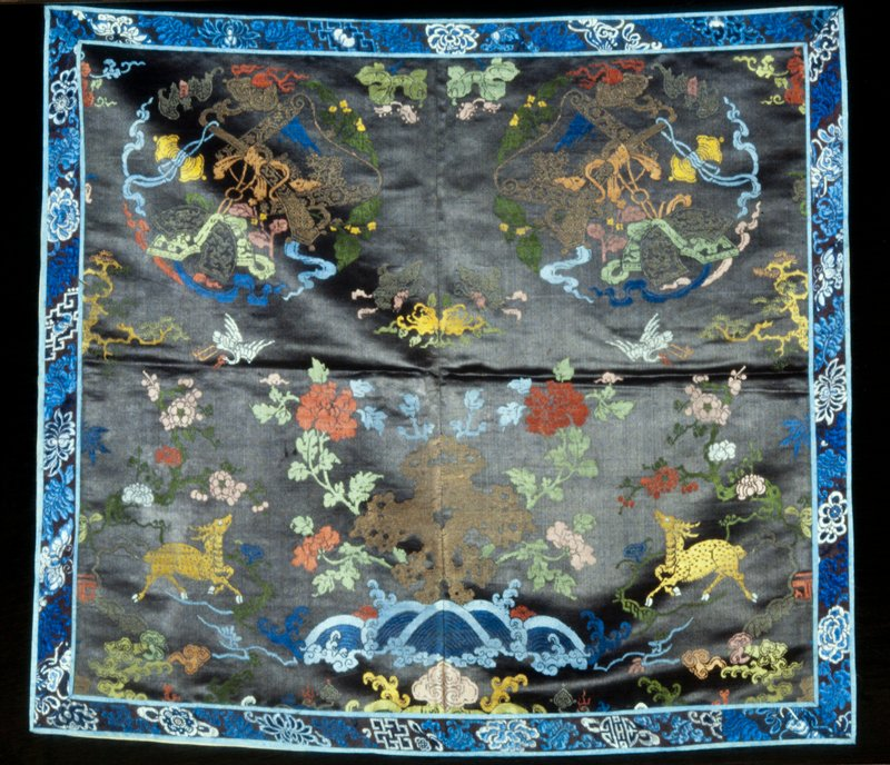 Panel of taupe satin brocade. The design includes two medallions containing religious symbols in upper right and left corners. Cranes, bats,, sprays of plum blossom, pine and two spotted deer in lower right and left corners. In lower center a gold cloud, from which spring peony blossoms above a line of rolling waves. Colors include shades of blue, green, pink, red, and yellow, as well as gold threads. Border of faded plum satin embroidered with blossoms and symbols in shades of blue and white. Piece made of two sections seamed up the middle and lined with thin peach-colored silk.