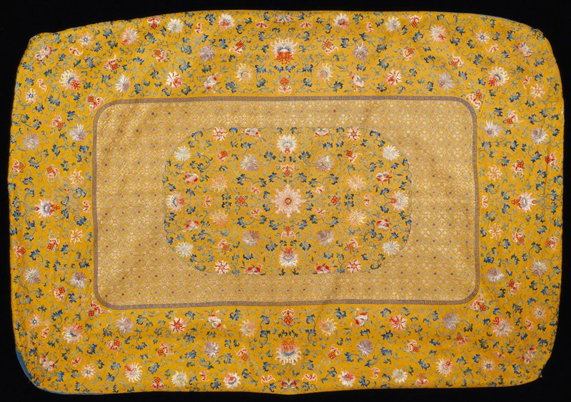 Throne seat cover of embroidered imperial yellow silk. Oblong central panel set off from outer area by a running meander in bright dark blue. Central portion of panel has design of large flowers and trailing leaves, bats, double peach, swastika and other good luck emblems on plain ground. Bordering it the ground has an all-over pattern of medallions, lozenges and flowers producing a diaper. The outer border is embroidered with the same large floral and symbol pattern used in innermost panel. Chiefly satin stitch. Colors include shades of blue, pink, green, gray, violet, red, yellow and apricot. Boxed border of medium blue satin; lining of yellow satin. Badly stained by mildew. Cf. 42.8.155. Undoubtedly part of a set.