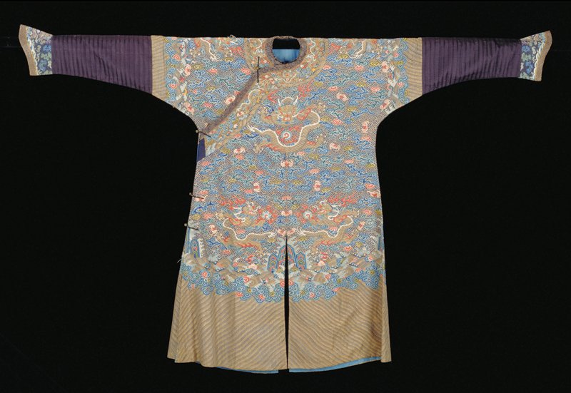 Imperial robe of blue k'ossu with gold swastika-fret diaper ground. Nine 5-clawed dragons in gold, those in profile clutching the Heavenly Jewel. On the ground are scattered loose clouds and bats in shades of blue, green, red, pink, soft violet, olive green and yellow. Conventional border of slightly wavy stripes in gold and black threads; tight clouds; rolling waves in gold and black threads with symbols of the Eight Precious Things and branches of coral. Below border on sleve, a strip of blister ribbed black silk. Cuffs of greyed-blue K'ossu with bats, clouds, dragons etc. Note stronger violet color in cuffs which are obviously a later addition. Collar band is of black K'ossu with body designs and is edged with blue and gold brocade. Coat slit front and back and lined with thin blue silk. K'ossu badly broken on right shoulder.