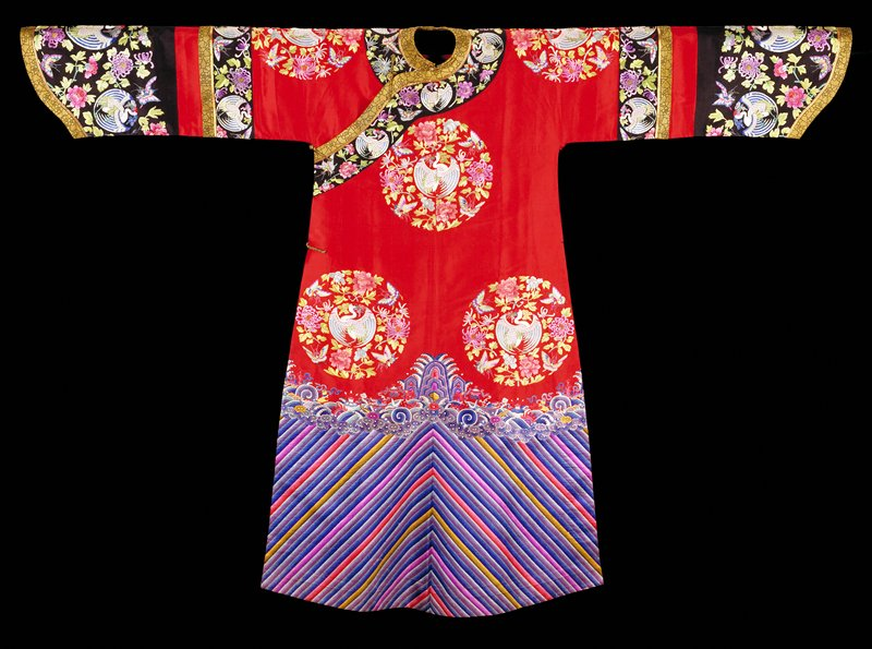 Robe of red twilled silk embroidered with eight large medallions containing cranes, butterflies, chrysanthemum and peony sprays in shades of pale blue, green, rose, lavendar, and magenta. Conventional border of straight, slanting stripes; tight clouds; rolling waves with Buddhist symbols, swastikas, branches of coral and emblems of the Eight Precious Things. Colors very crude and strong. Wide deep cuffed sleeves with a band of black silk embroidered with the medallion motifs and finished at lower edge with band of gold and black brocade. Directly below a band of the red silk separates this from the cuff, also of black silk and embroideded with the medallion motif. Collar band of the same, both edged with black and gold brocade. Robe is slit at sides, unlined but faced back with bands of the embroiedred silk. A woman's coat?