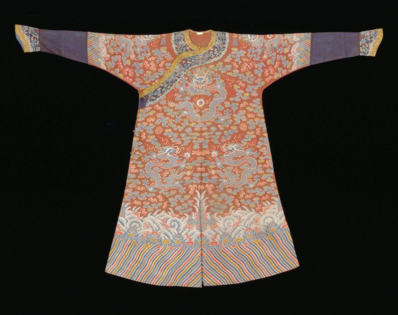 Imperial Robe of rust colored gauze embroidered in needlepoint. Nine 5-clawed dragons in blue , those in profile clutching the Heavenly Jewel. In the ground loose clouds, bats - some in groups of five - and longevity characters in shades of blue, green, yellow, pink, olive green, and rust. Conventional border of slightly wavy slanting lines; tight clouds, and curling waves in which appear groups of bats. Below border on sleeves a strip of plain black gauze lined in blue. Cuffs and collar band of dark blue gauze embroidered with body designs. Edging of gold and black floral brocade.Coat slit back, front and sides. Unlined but faced back with the embroiderd gauze.