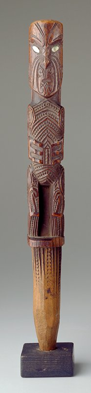 stakelike small staff, carved to slight point at bottom; standing figure, scowling with hands on stomach, covered in incised tattoos; abalone eyes; back decorated with triangles and linear design; attached to mount