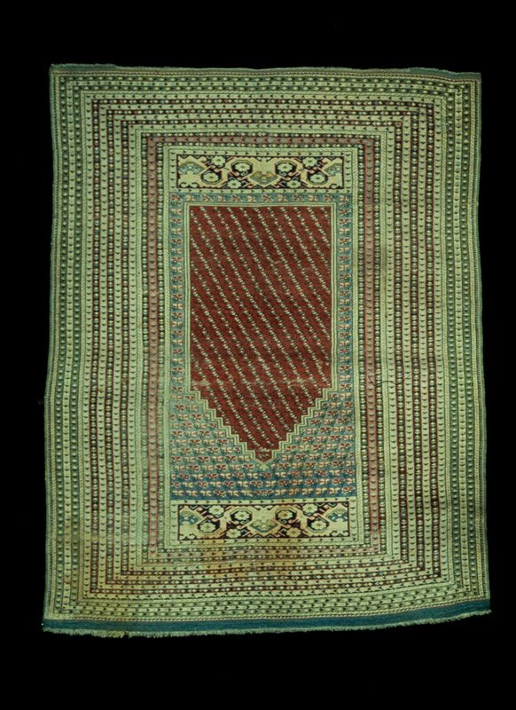 Prayer Rug, Kulah. The prayer field of rose-red is filled with diagonal rows of stiff floral motifs in soft green. The area above and around the prayer field is soft blue, becoming darker at top, with rows of single flowers in red and white. Above and below the main field is a variation of the typical Kulah S-scroll border with single blossoms on a dark blue ground. The border contains 18 narrow stripes of rose, white, brown and green filled with conventionalized blossoms and geometric motifs. Sides selvaged and the ends finished with a narrow web fringed with warp threads. Ghiordes knot with 12 knots per lineal inch. Wool warp and woof. Nap well worn down.