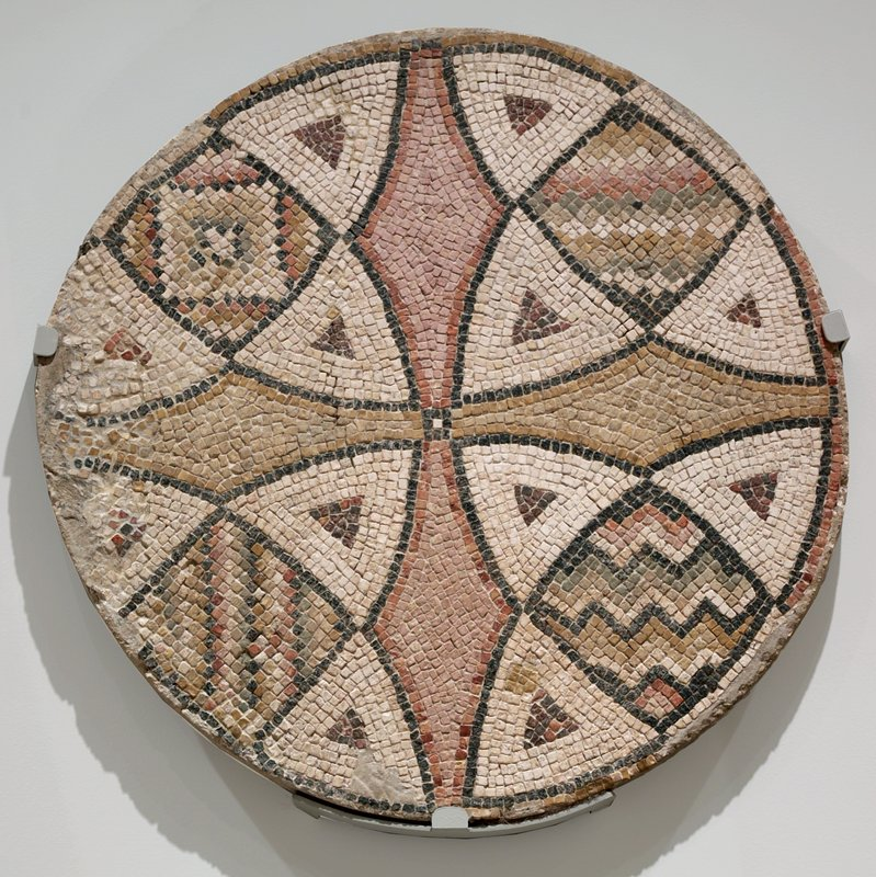 Mosaic, stone, granite, on metal brace mount, stored flat; mount incl in msmts.; Byzantine mosaic representing a stylized cross in multicolors excavated in northern Syria near Antioch which, at the period of these churches, was Turkish Territory. Round.