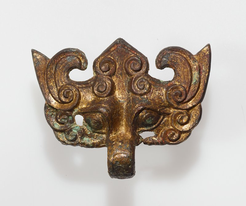 T'ao Tieh mask, with pendant ring; large figure decoration on mask partly obliterated by heavy brown and green encrustiation; bronze cracked to left of right eyebrow; gilt bronze.