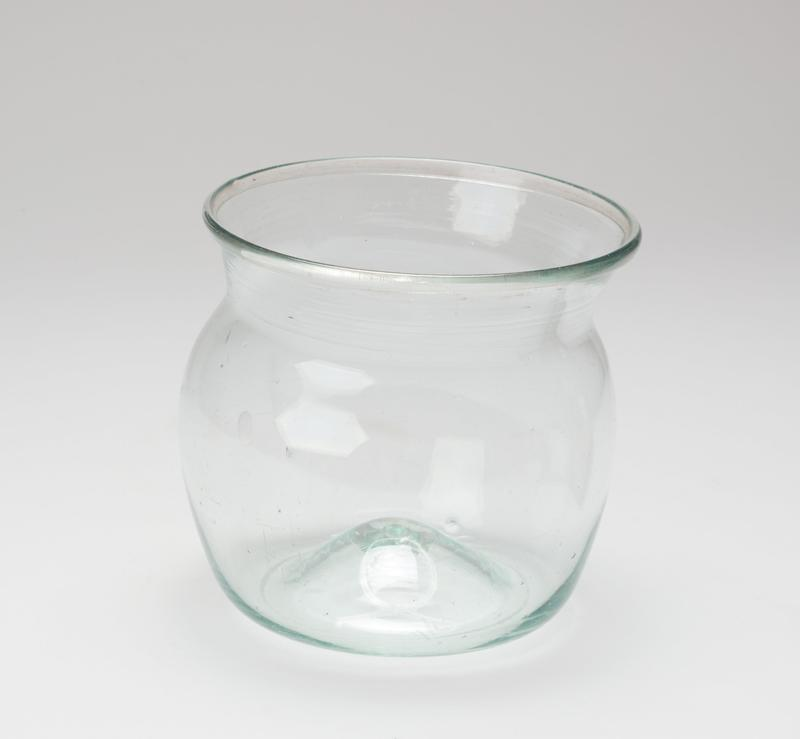 Glass bowl with green tint; round shape with short neck below protruding lip; raised center; slightly irregular proportions.