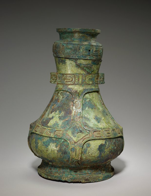 The decor displays outstanding elements of the Middle Chou repertoire on a vessel reminiscent in profile of an earlier Hu (50.46.26, Karlgren number 19). An eyed band with diagonals appears on the foot and on the belly is a system of scale bands in flat relief, imitating straps around the flask. Big lozenges in high, peaked relief occur at the junction of these bands. An identical scale band decorates the neck, which has, in its narrowest part, two small handles. These, with two free animals' heads, achieve a division into four sections. The handles are adorned with t'ao-t'ieh heads (rare int he Middle Chou style and usually found on such accesory parts as handles or legs). The scale band is repeated for the third time on the lid a functional member in that the ring-shaped top can serve as a foot if the lid, inverted, is turned into a cup. Patina green with patches of red.