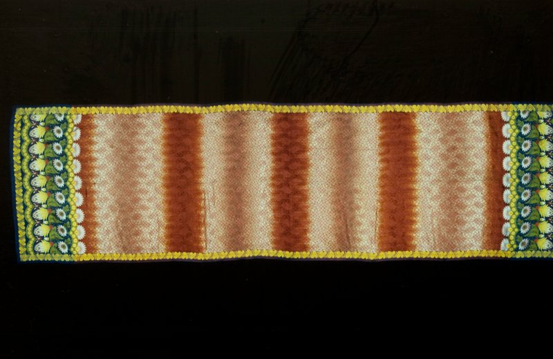 Sari, rust and beige silk with gold leaf border on sides and elaborate floral border at ends. Blue silk fringe at both ends. Fringe is 2 inches wide.