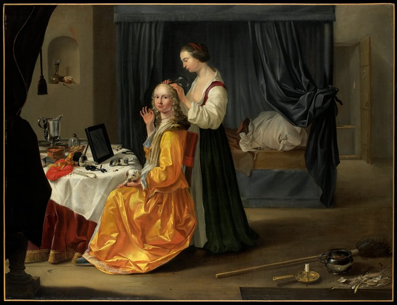 Genre. Interior of a bedroom with a lady dressed in bright golden yellow silk, a small dog in her lap, seated at a dressing table with toilet articles on it. A maid pinning a bow into her long wavy blonde hair is standing behind her. In the background a canopied bed with gray draperies.